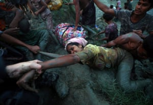 Photographers help a Rohingya woman out of the Naf river as refugees cross the Myanmar-Bangladesh border in Palong Khali, near Cox's Bazar