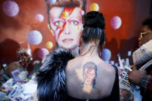 A woman with a Ziggy Stardust tattoo visits a mural of David Bowie in Brixton