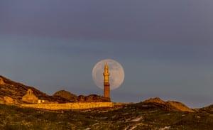 Full moon rises behind Kucuk and Ulu Mosques, in Palu district of Elazig, Turkey