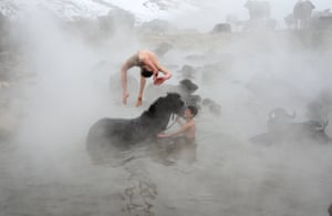 Bitlis, Turkey: A boy dives into hot spring water where buffaloes are gathered for cleaning