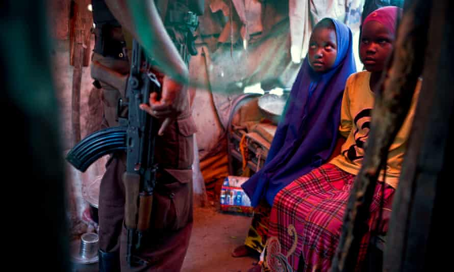 Two young girls with a security guard in their temporary shelter in a settlement for internally displaced people near the airport in Mogadishu.