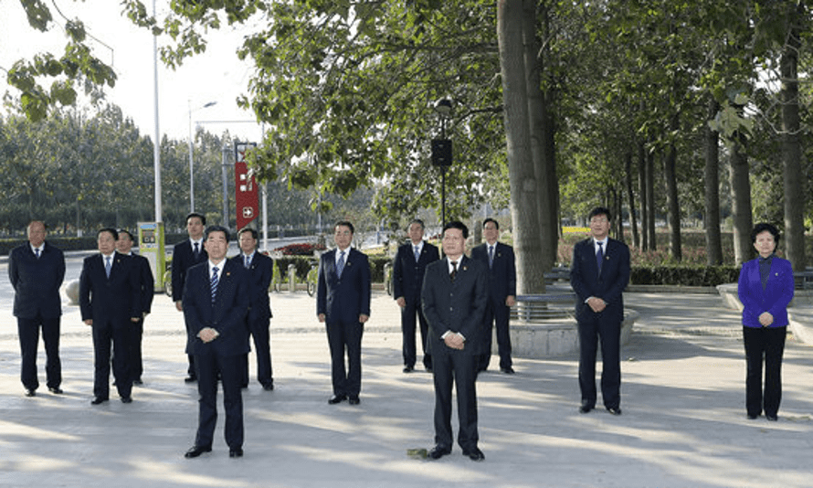 Officials stand in front of a tree which was planted by Chinese president Xi Jinping