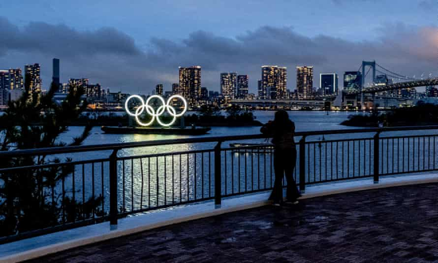 A person gazes at the Olympic logo during the coronavirus lockdown in Tokyo.