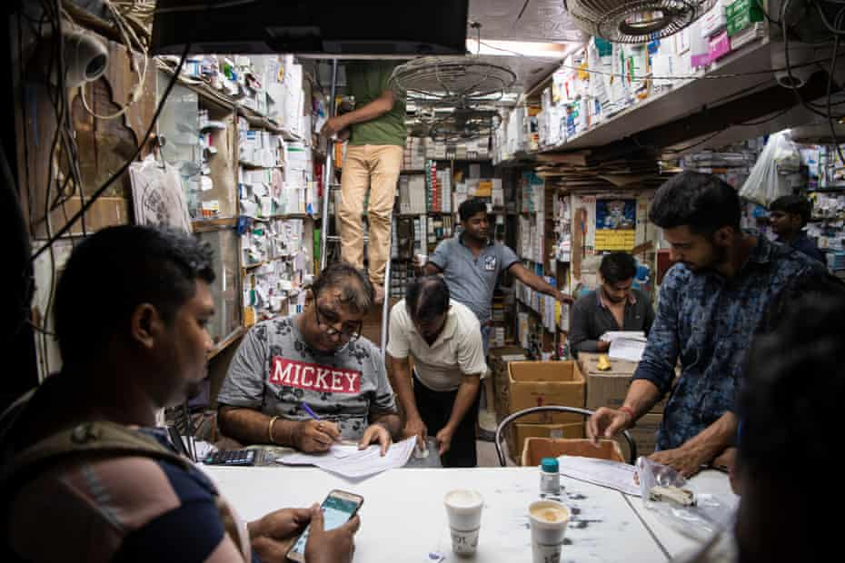 Shopkeepers at a pharmacy shop at Bhagirath Palace's pharmaceuticals market in Old Delhi.