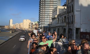 Tourists take in the sights from a tour bus of Havana. Cuba is ready to welcome American visitors legally after half a century.