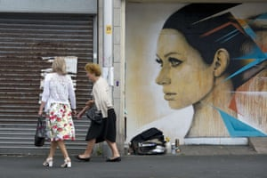 Women walk past a piece of street art in Blackpool.