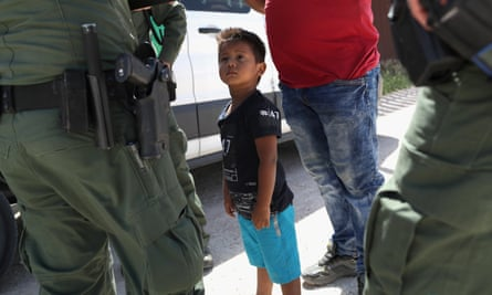 A boy and father from Honduras are taken into custody by US Border Patrol agents near Mission, Texas.