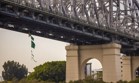 An activist from Extinction Rebellion dangles from the Story Bridge in a hammock as part of protests in Brisbane on Tuesday