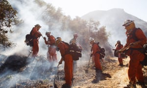 Firefighters work to extinguish a flare-up of the Woolsey Fire on a hillside in West Hills