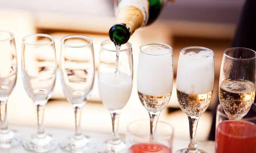 A waiter filling champagne glasses