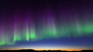 Multicoloured aurora reach upwards.