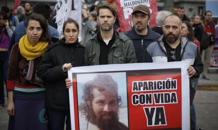 """Relatives of Santiago Maldonado and activists hold photos of Maldonado and the Spanish message """"Appear alive now"""" as they protest his disappearance on Monday."""