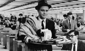 Jack Lemmon in a suit and trilby, carrying a pile of files and notebooks, a raincoat thrown over his shoulder, as he walks through a large, busy office, in The Apartment. Black and white