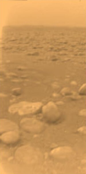 14 January 2005An image by the European Space Agency's Huygens probe, which accompanied Cassini to Saturn, during its successful descent to land on the moon Titan. Initially thought to be rocks or ice blocks, the visible objects are more pebble-sized. The surface is darker than originally expected, consisting of a mixture of water and hydrocarbon ice. There is also evidence of erosion at the base of these objects, indicating possible fluvial activity. This view gives an indication of the actual colour of the surface.