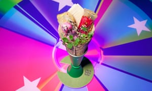 A cone containing bright coloured jellied sticks in the centre of a multi-coloured 'pie chart' background