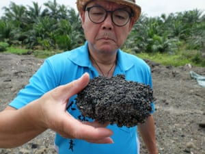 C.K. Lee, a lawyer and activist, with burned plastic residue in Kuala Langat.