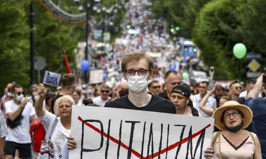A man holds poster reading 'Putinizm' during a protest in support of Sergei Furgal, the governor of the Khabarovsk region