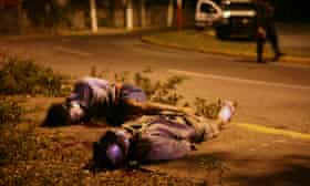 Two men with their hands tied behind their back and with their faces covered with duct tape lie by the side of the road as police secure the area in the city of Veracruz on 6 December 2011.