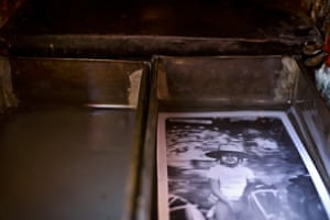 A portrait lays in fixer as it's developed inside Luis Maldonado's old wooden box camera