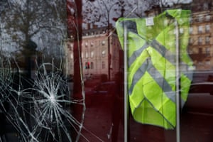 A yellow vest hangs inside a vandalised store front