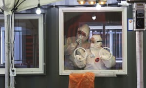 Medical workers in a booth work during COVID-19 testing at a makeshift clinic in Seoul, South Korea on Saturday.