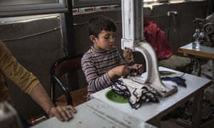 A small boy makes shoes in the factory