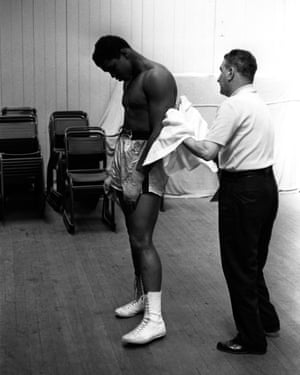 Cassius Clay is towelled-down by a corner man.