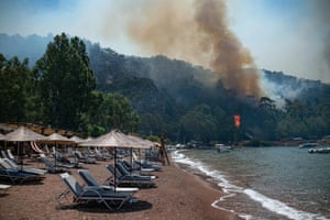 Deckchairs on a beach near a forest fire in Mugla province, Turkey