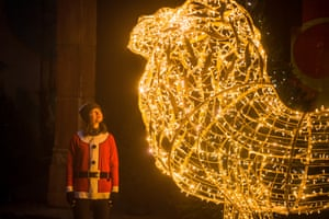 London, UKA woman poses next to a lit up sculpture of a lion as it is part of the Christmas lights display at ZSL London Zoo