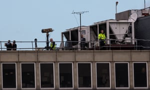 Police officers and others stand near equipment on the rooftop of a building as the runway is reopened at London Gatwick Airport on December 21.