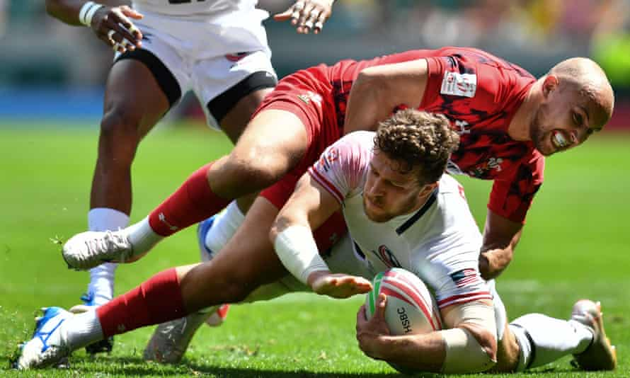Steve Tomasin of the USA is tackled by Wales' Luke Terharne at Twickenham.