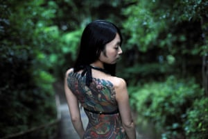 Model Yuki displays her tattoos at a park in Tokyo
