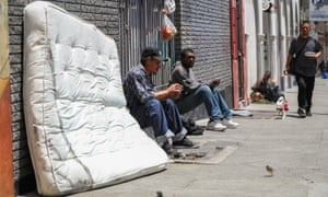 Felix Estrada Garcia, left, sits on the sidewalk in the Tenderloin in San Francisco. More than 70 people in the city's master voting list cite General Delivery as their mailing address.