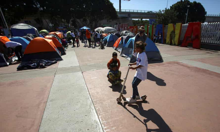 Children play next to migrants from Central America hoping to cross into the US, at their campsite outside El Chaparral border crossing, in Tijuana, Mexico, on 27 February.