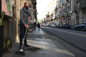 A store owner sweeps up ash that fell on Tuesday during an eruption of Mount Etna
