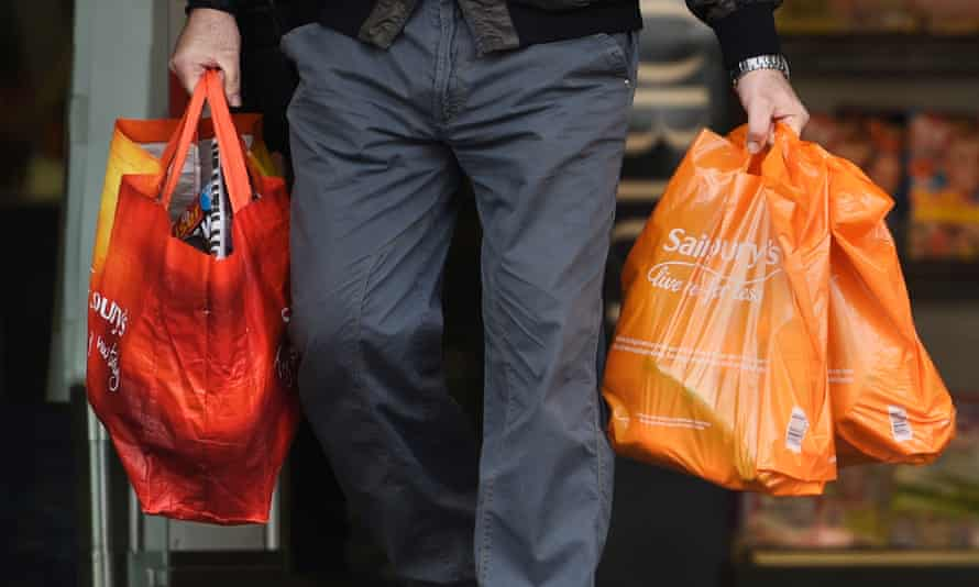 Man holding Sainsbury's bags