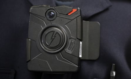 A police officer demonstrates the use of a body camera.