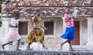 Schoolgirls run in front of an old Portuguese villa on Ibo island, part of the Quirimbas archipelago, Mozambique, 2007