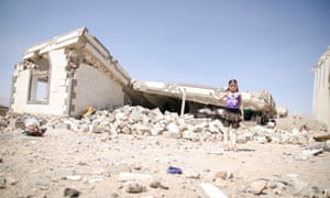 Raja'a*, seven, in front of her destroyed home in Yemen