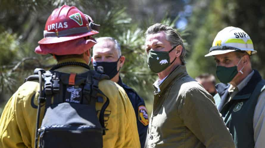 Governor Gavin Newsom talks with local and state fire officials while touring an area burned by last year's Creek fire near Shaver Lake in Fresno county, California.