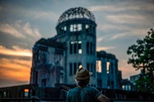 Hiroshima, Japan: A man plays his guitar in front of ruins of the Hiroshima Peace Memorial
