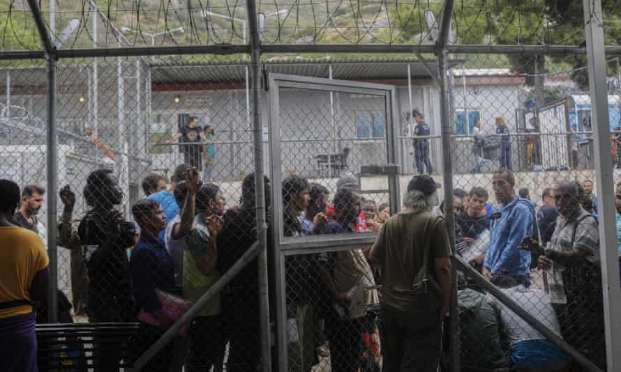 People queuing outside the information office at a refugee and migrant camp on the Greek island of Samos.
