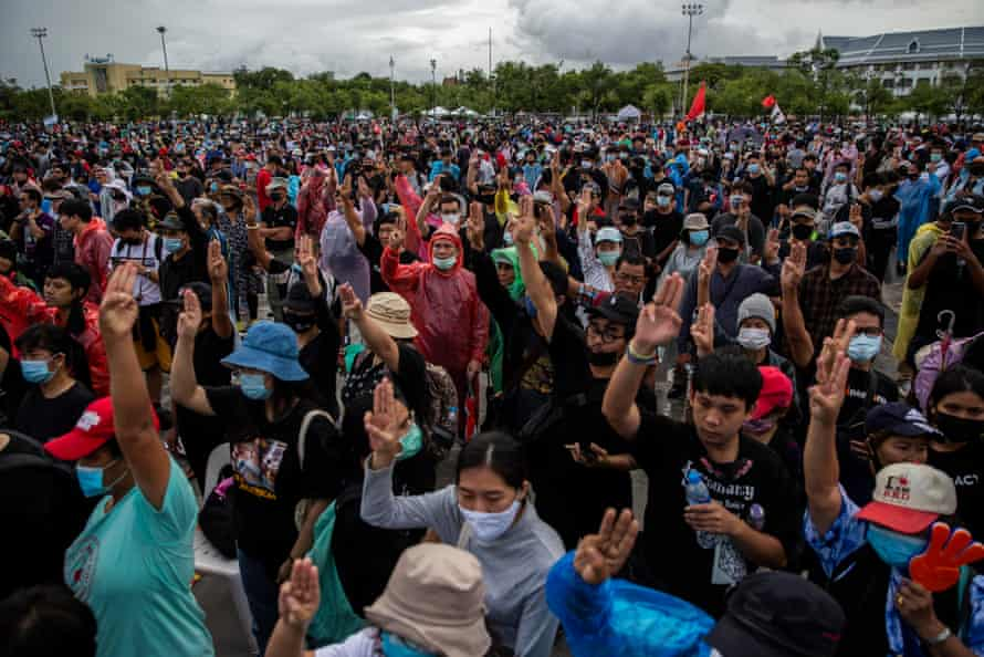 Anti-government protesters hold up a three-finger salute during a rally at Sanam Luang on Sunday.