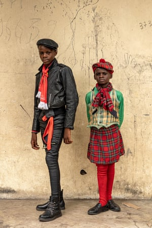 Francis Okiemi, 14-year-old school student and sapeur for three years, Steven Okiemi, nine-year-old school student and sapeur for one year, in Brazzaville. Francis wears a jacket by Janbell, trousers by Timing, shirt by Rabee, hat by Canda, scarf by Coca Cola and shoes by Botini. Steven wears kilt, hat and scarf from Scotland, shirt by Miss Dolce, locally made waistcoat and shoes by Gorila