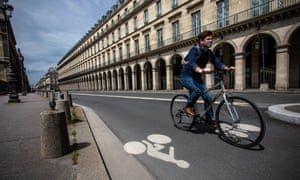A man rides a bicycle on Paris's Rue de Rivoli, where cars have been banned. Cycling is being encouraged in Paris to reduce overcrowding on trains and buses, and the city has opened temporary bike lanes.