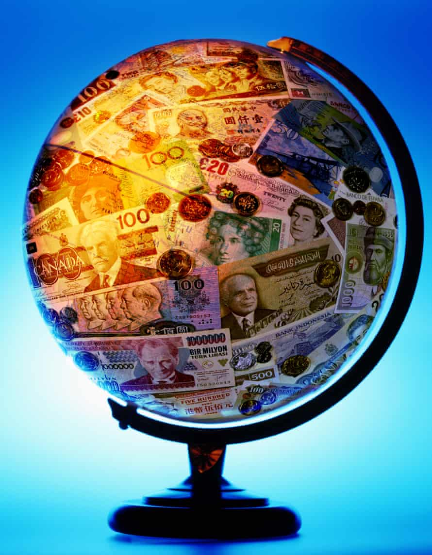 A desktop globe covered in banknotes and coins of various different countries