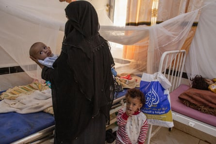Fatima Mohammad holds her four-year old granddaughter Sara Nasser, who is suffering from a chest infection, in the paediatrics ward of Ataq General Hospital