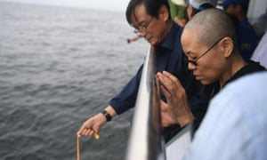 Liu Xia (front) was last seen in photos issued by Beijing as her husband's ashes were scattered at sea off the coast of Dalian, Liaoning province.