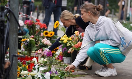 People lay flowers at the site of a car accident in Berlin, Germany.