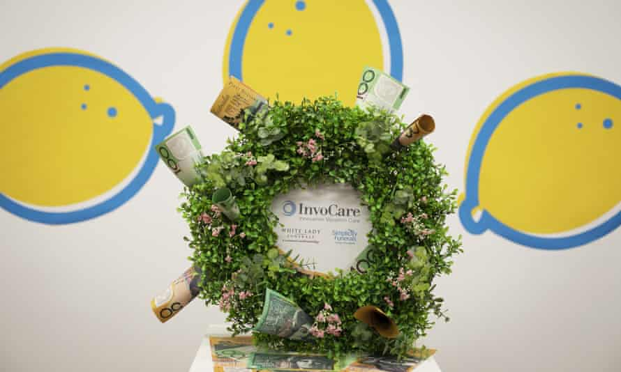 A mock funeral wreath surrounded by money over the InvoCare logo. InvoCare are one of the 'winners' of the 2020 Shonky awards for 'profiting from keeping grieving families in the dark'.